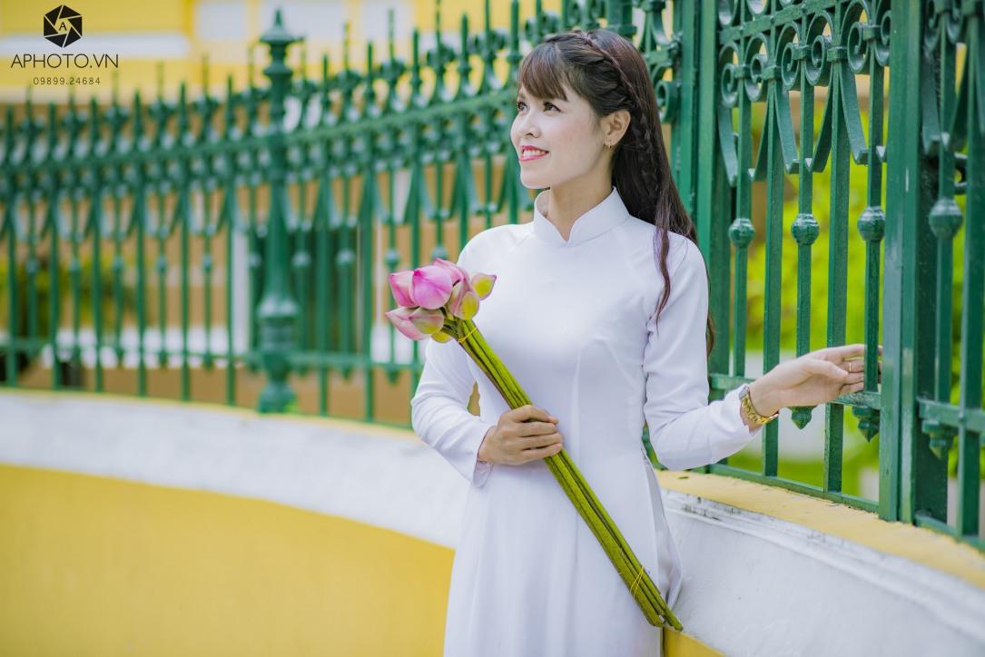 Tạo dáng cầm hoa với áo dài