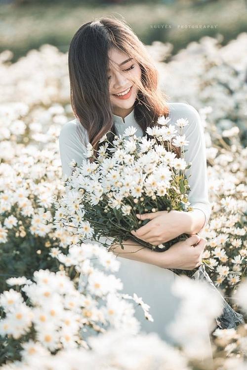 Đứng bên hoa, nhắm mắt tạo dáng