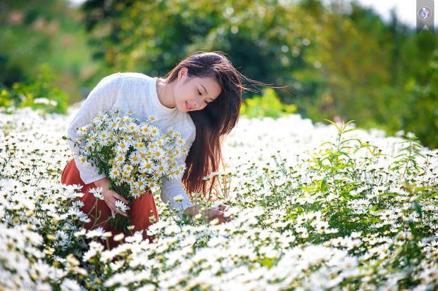 Đi giữa vườn hoa, nghiêng người tay nâng bông hoa